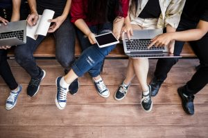 College students sitting together looking at computers and notebooks.