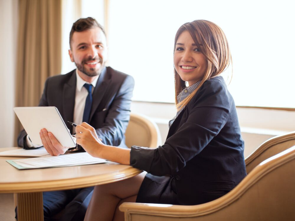 Man and woman in a business meeting sitting at a table.